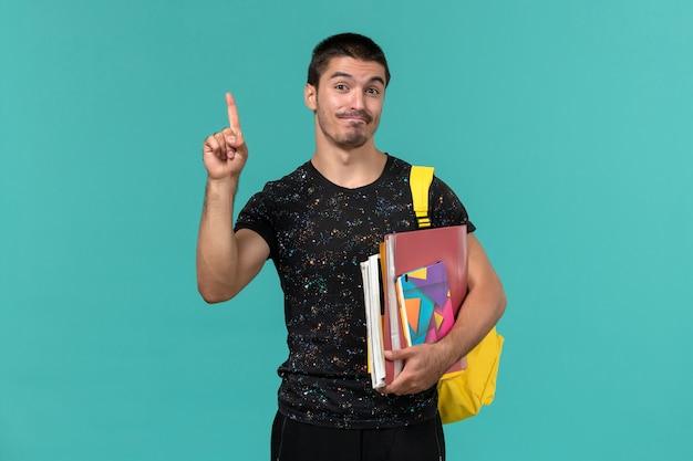 Vista frontal de um estudante do sexo masculino em uma mochila de camiseta amarela escura segurando um caderno e arquivos na parede azul