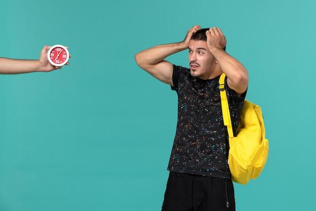 Vista frontal de um estudante do sexo masculino na mochila de camiseta amarela escura olhando para os relógios na parede azul clara