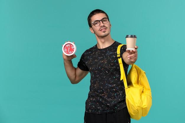 Vista frontal de um estudante do sexo masculino na mochila de camiseta amarela escura segurando café e relógios na parede azul