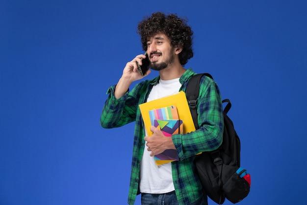 Vista frontal de um estudante do sexo masculino usando uma mochila preta segurando cadernos e arquivos falando ao telefone na parede azul-clara