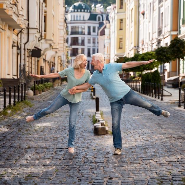 Vista frontal de um feliz casal de idosos aproveitando o tempo na cidade