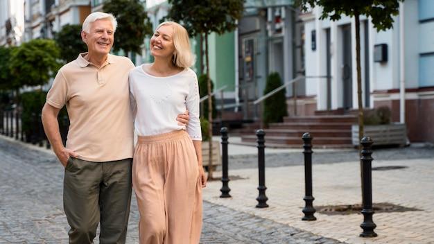 Vista frontal de um feliz casal de idosos dando um passeio pela cidade