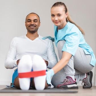 Vista frontal de um fisioterapeuta masculino e feminino fazendo exercícios