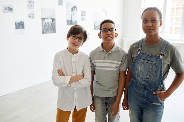 Vista frontal de um grupo diversificado de crianças olhando para a arte em uma galeria moderna, copie o espaço