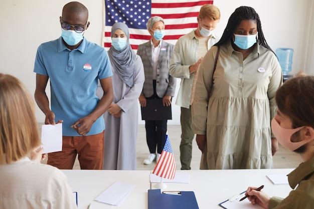 Vista frontal de um grupo multiétnico de pessoas em pé em uma fila e usando máscaras na seção eleitoral no dia da eleição, com foco em dois afro-americanos que se registram para votar