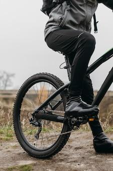 Vista frontal de um homem andando de bicicleta na montanha