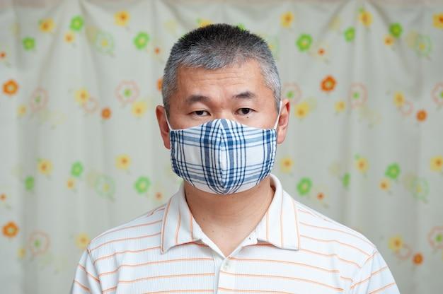Vista frontal de um homem asiático de meia-idade usando máscara facial de tecido faça você mesmo