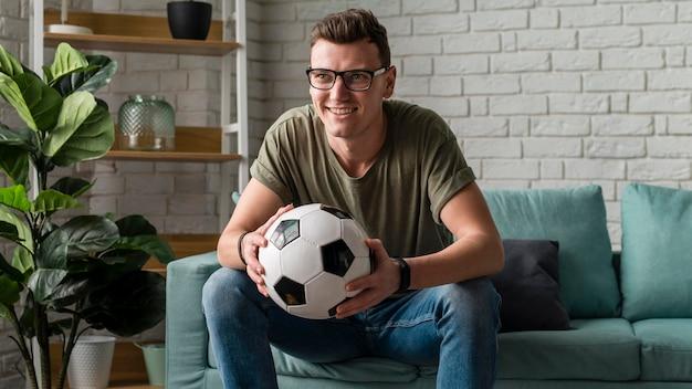 Vista frontal de um homem assistindo esportes na tv enquanto segura uma bola de futebol
