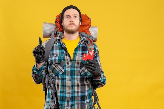 Vista frontal de um homem barbudo com um mochileiro segurando um cartão de crédito apontando para o teto