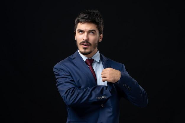 Vista frontal de um homem barbudo confuso em um terno procurando algo no bolso, dentro do terno, na parede escura