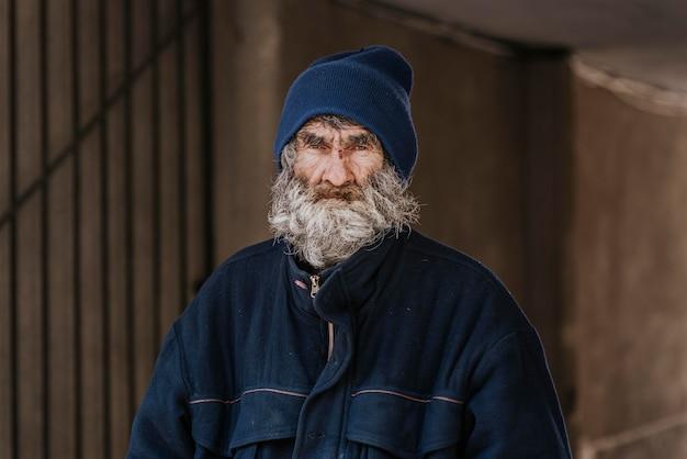 Vista frontal de um homem barbudo sem-teto na rua