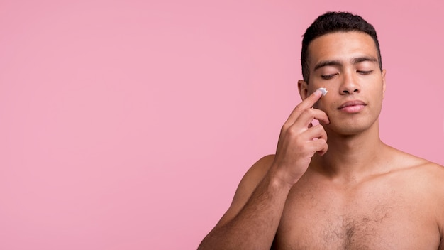 Vista frontal de um homem bonito aplicando creme facial com espaço de cópia