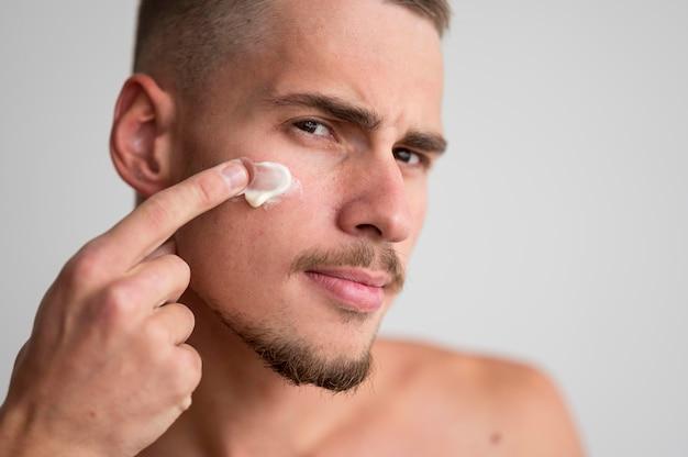 Vista frontal de um homem bonito aplicando creme facial