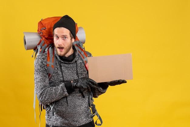Vista frontal de um homem bonito caroneiro com luvas de couro e uma mochila segurando um papelão em branco