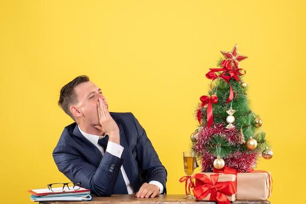 Vista frontal de um homem bonito chamando alguém sentado à mesa perto da árvore de natal e presentes em amarelo
