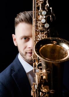 Vista frontal de um homem bonito com o saxofone na parede preta backgroung isolado