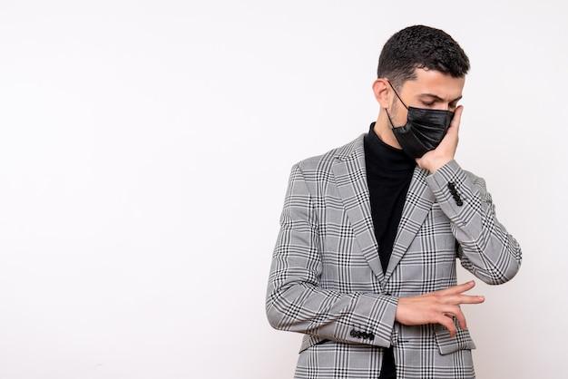 Vista frontal de um homem bonito de terno segurando o rosto em pé sobre um fundo branco isolado