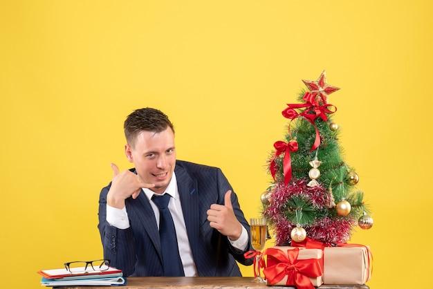 Vista frontal de um homem bonito, fazendo sinal para me ligar, sentado à mesa perto da árvore de natal e presentes em amarelo