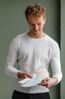Vista frontal de um homem bonito planejando redecorar a casa usando a paleta de tinta