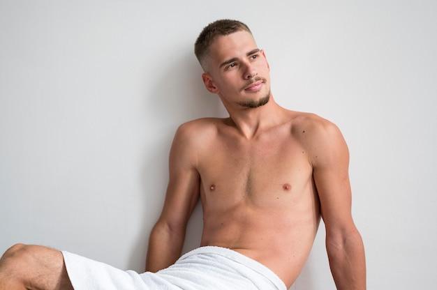Vista frontal de um homem bonito posando sem camisa em uma toalha