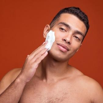Vista frontal de um homem bonito sem camisa aplicando espuma de barbear