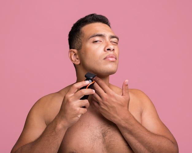 Vista frontal de um homem bonito usando um barbeador elétrico