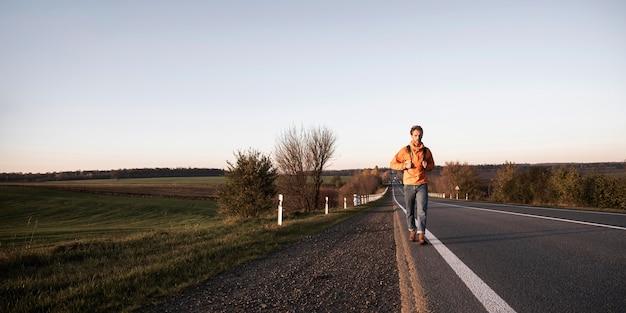 Vista frontal de um homem caminhando sozinho na estrada