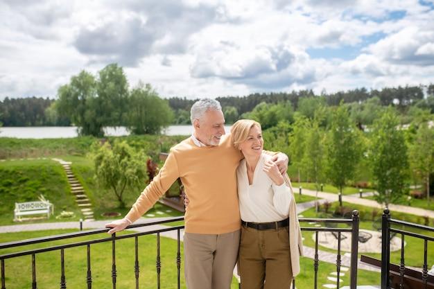 Vista frontal de um homem caucasiano de cabelos grisalhos, alegre, bonito, abraçando uma mulher loira atraente e elegante no terraço