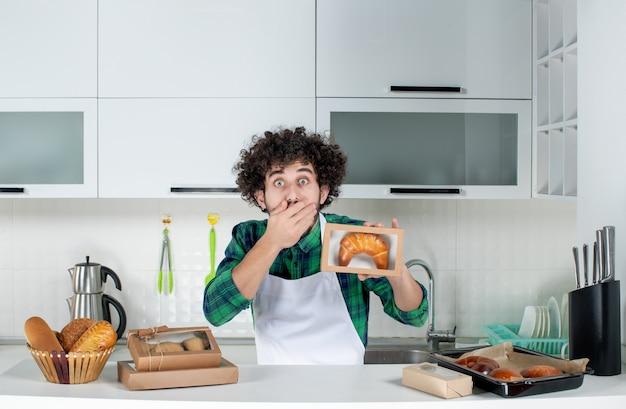Vista frontal de um homem chocado segurando uma massa recém-assada em uma pequena caixa na cozinha branca