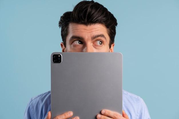Vista frontal de um homem cobrindo o rosto com um tablet