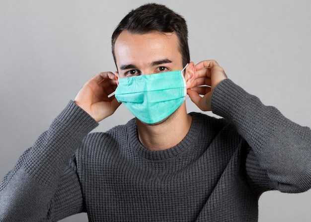 Vista frontal de um homem colocando máscara médica no rosto