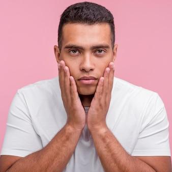 Vista frontal de um homem com as palmas das mãos no rosto