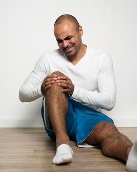 Vista frontal de um homem com dor no joelho