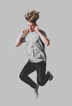 Vista frontal de um homem com fones de ouvido pulando no ar