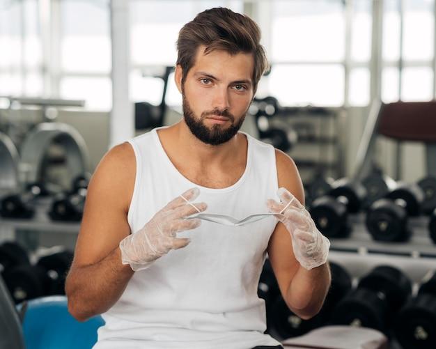 Vista frontal de um homem com luvas colocando máscara médica na academia
