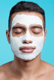 Vista frontal de um homem com máscara facial de beleza