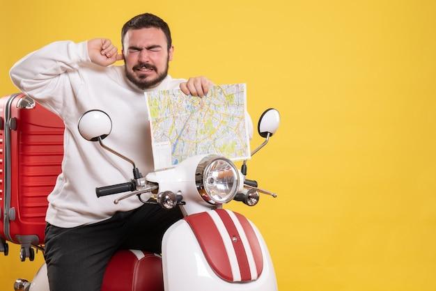 Vista frontal de um homem com problemas sentado em uma motocicleta com uma mala segurando um mapa que sofre de dor de ouvido em fundo amarelo isolado