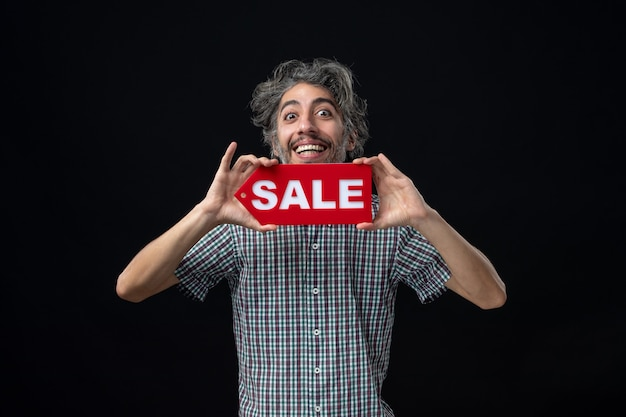 Vista frontal de um homem com um sorriso segurando uma placa de venda em pé na parede escura