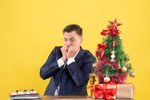 Vista frontal de um homem confuso sentado à mesa perto da árvore de natal e presentes em amarelo