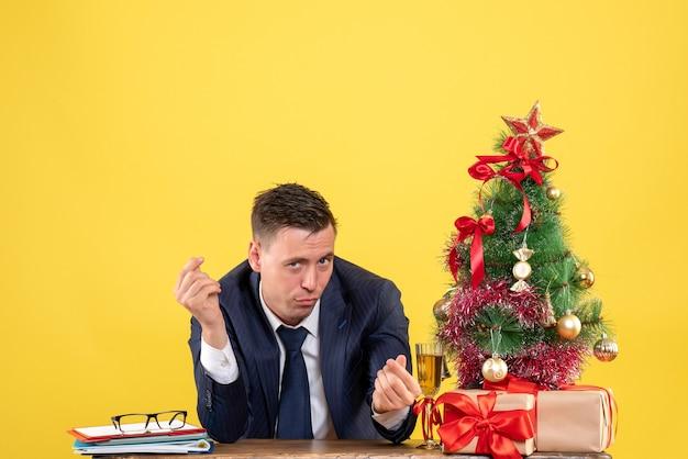 Vista frontal de um homem curioso fazendo sinal de dinheiro sentado à mesa perto da árvore de natal e presentes em amarelo