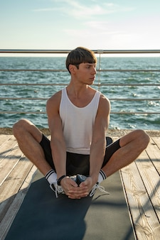 Vista frontal de um homem de camiseta regata malhando na praia