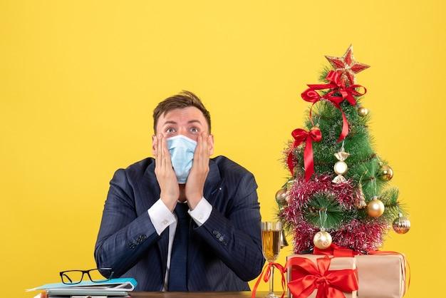 Vista frontal de um homem de negócios chocado olhando para cima, sentado à mesa perto da árvore de natal e presentes em amarelo