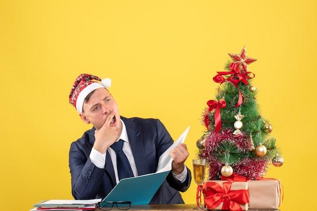 Vista frontal de um homem de negócios confuso sentado à mesa perto da árvore de natal e presentes em amarelo