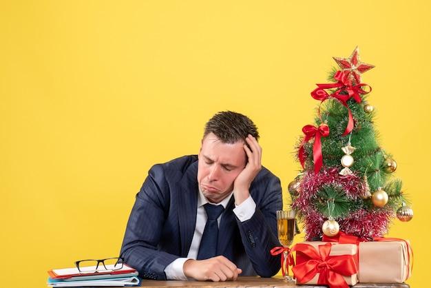 Vista frontal de um homem deprimido fechando os olhos, sentado à mesa perto da árvore de natal e presentes em amarelo