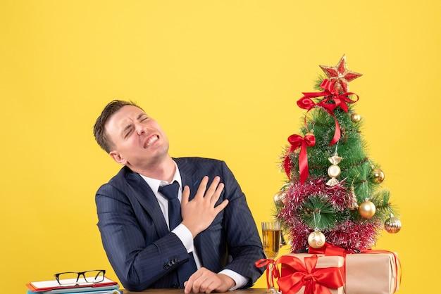 Vista frontal de um homem deprimido segurando o peito com dor, sentado à mesa perto da árvore de natal e presentes em amarelo