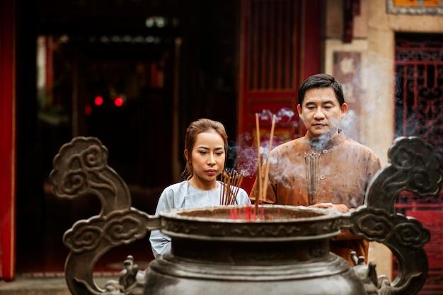 Vista frontal de um homem e uma mulher com incenso no templo