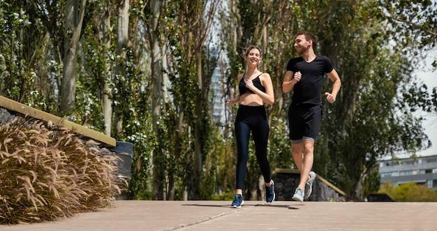 Vista frontal de um homem e uma mulher correndo juntos ao ar livre