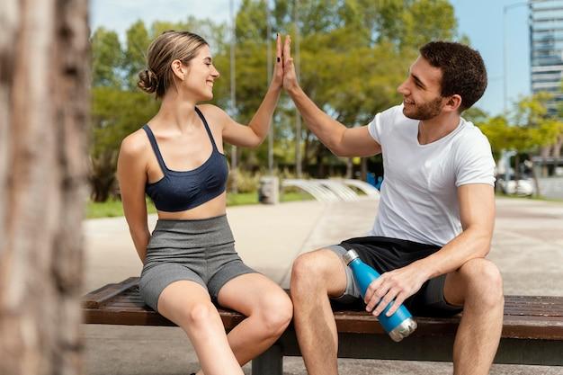 Vista frontal de um homem e uma mulher descansando ao ar livre após se exercitarem e cumprimentando um ao outro