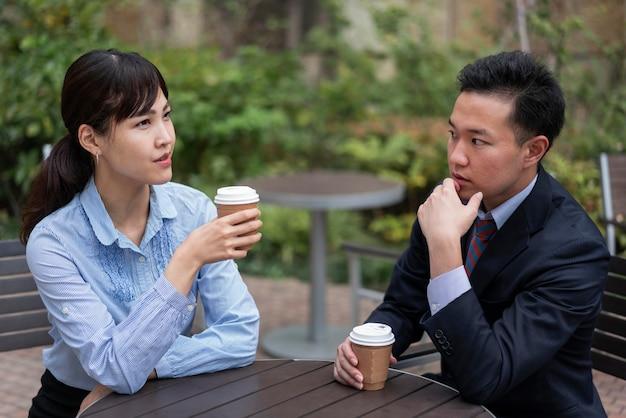 Vista frontal de um homem e uma mulher discutindo à mesa