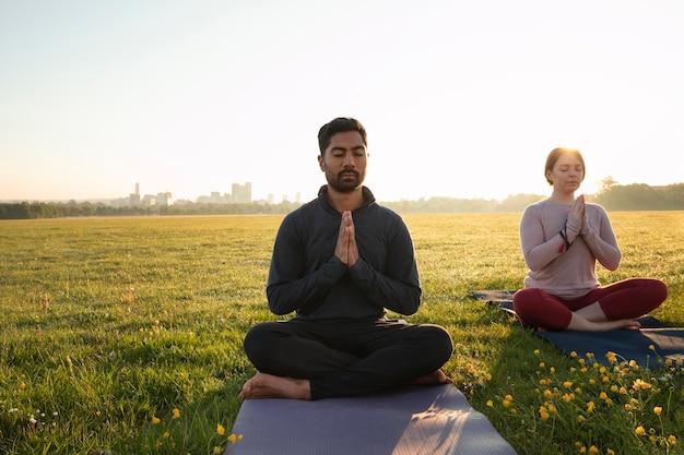 Vista frontal de um homem e uma mulher meditando ao ar livre
